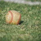 white and red baseball on green grass