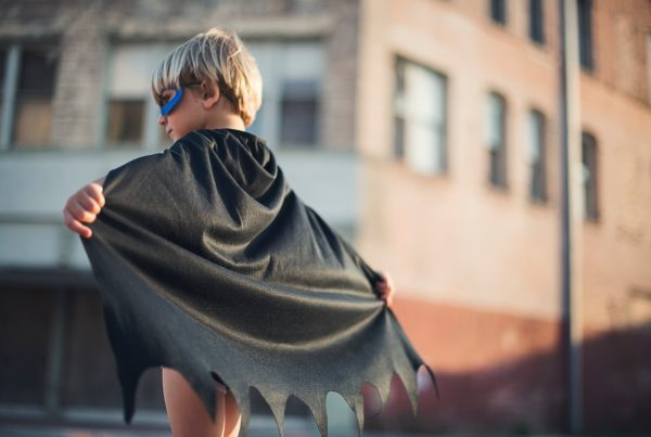 selective focus photography of boy wearing black Batman cape